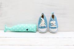 Jouez les chaussures bleues du ` s de baleine et d'enfants sur un fond en bois blanc Photographie stock libre de droits