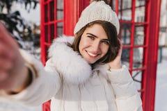 Jouful όμορφο κορίτσι πορτρέτου Selfie στο άσπρο μάλλινο καπέλο που απολαμβάνει το ηλιόλουστο χειμερινό πρωί στο κόκκινο υπόβαθρο στοκ εικόνες