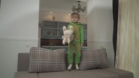 Jouful little boy in green pajamas jumping on the sofa at home. Child grabs pillow and throws in on the floor. Happy. Cute small boy in green pajamas jumps on stock video