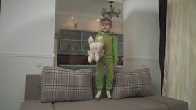 Jouful weinig jongen die in groene pyjama's op de bank thuis springen Het kind grijpt hoofdkussen en werpt binnen op de vloer gel stock video