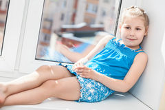 Jouful young girl in blue dress laying on window Stock Photos