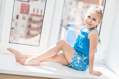 Jouful young girl in blue dress posing on window Royalty Free Stock Image