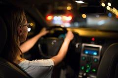Joung kvinna som kör hennes moderna bil på natten arkivfoto