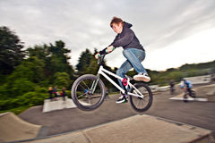 Joung red haired boy is jumping with his BMX Bike Stock Images
