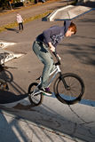 Joung red haired boy jumps with his BMX Bike at the skate park Stock Image