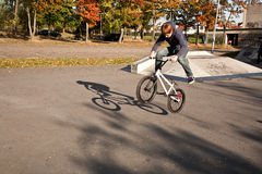 Joung red haired boy jumps with his BMX Bike at the skate park Royalty Free Stock Photos