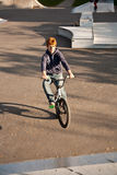 Joung red haired boy jumps with his BMX Bike at the skate park Stock Photography