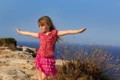 Jour bleu avec les mains ouvertes de fille de gosse au vent Photos stock