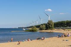 Jour d'été avec des personnes sur la plage néerlandaise avec les turbines de vent viables d'énergie dans le bakground Photo stock