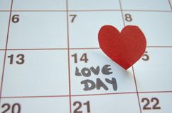 Jour d'amour - coeurs rouges de papier marquant le jour de valentines du 14 février sur le calendrier blanc photo stock