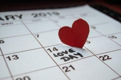 Jour d'amour - coeurs rouges de papier marquant le jour de valentines du 14 février sur le calendrier blanc photos stock