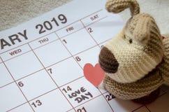 Jour d'amour - coeurs rouges de papier marquant le jour de valentines du 14 février sur le calendrier blanc avec le chiot mou de  image libre de droits