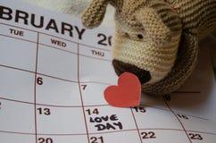 Jour d'amour - coeurs rouges de papier marquant le jour de valentines du 14 février sur le calendrier blanc avec le chiot mou de  image stock
