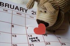 Jour d'amour - coeurs rouges de papier marquant le jour de valentines du 14 février sur le calendrier blanc avec le chiot mou de  images stock