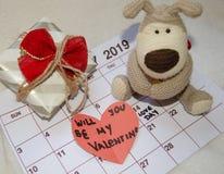 Jour d'amour - coeurs rouges de papier marquant le jour de valentines du 14 février sur le calendrier blanc avec le chiot mou de  photos stock