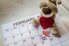 Jour d'amour - coeurs rouges de papier marquant le jour de valentines du 14 février sur le calendrier blanc avec le chiot mou de  images libres de droits