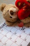 Jour d'amour - coeurs rouges de papier marquant le jour de valentines du 14 février sur le calendrier blanc avec l'ours de nounou photos stock