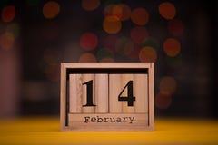 Jour 14 d'ensemble de février sur le calendrier en bois avec le bokeh de guirlande sur le fond Fond de jour de valentines Photos stock