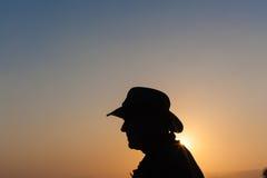 Jour d'homme au-dessus de silhouette de coucher du soleil Photographie stock libre de droits