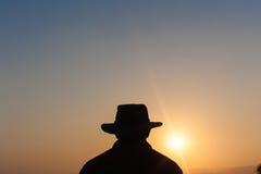 Jour d'homme au-dessus de silhouette de coucher du soleil Image stock