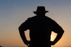 Jour d'homme au-dessus de silhouette de coucher du soleil Photo stock