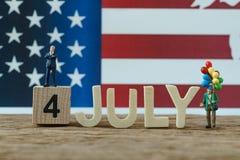 Jour de la Déclaration d'Indépendance Etats-Unis avec le vieil homme de personnes miniatures tenant le ballo Photos stock