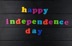 Jour de la Déclaration d'Indépendance heureux, lettres colorées sur le fond en cuir noir Photographie stock