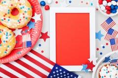Jour de la Déclaration d'Indépendance maquette heureuse du 4 juillet avec le drapeau américain et les nourritures douces, décorés Photographie stock
