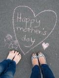 Jour de mères - dessin de craie de forme de coeur et les pieds d'un enfant photos libres de droits