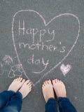 Jour de mères - dessin de craie de forme de coeur et les pieds d'un enfant Photographie stock