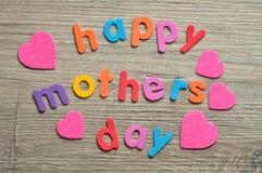 Jour de mères heureux dans les lettres colorées avec les coeurs roses Photographie stock