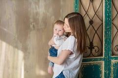 Jour de mères heureux Femme heureuse adorable avec le bébé posant dans les décorations modernes élégantes de studio Élément de co photo stock