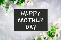 Jour de mères heureux Un tableau est entouré par les fleurs blanches sur un fond gris Image libre de droits
