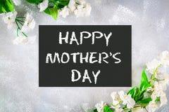 Jour de mères heureux Un tableau est entouré par les fleurs blanches sur un fond gris Photo stock