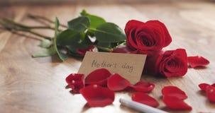 Jour de mères sur une carte de papier sur le vieux fond en bois avec des roses Images stock