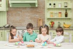 Jour de Pâques Un groupe d'enfants peignent des oeufs de pâques à la table dans la cuisine Photo libre de droits