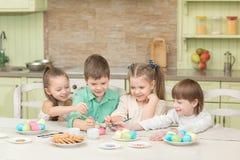 Jour de Pâques Un groupe d'enfants peignent des oeufs et le rire de pâques Photos libres de droits