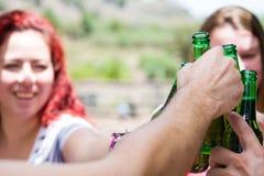 Jour de pique-nique avec des amis encourageant avec des bouteilles de bière Photos libres de droits