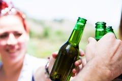 Jour de pique-nique avec des amis encourageant avec des bouteilles de bière Photographie stock libre de droits