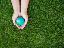 Jour de terre La terre à l'arrière-plan de mains et de champ d'herbe verte Envi Image libre de droits