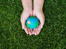 Jour de terre La terre à l'arrière-plan de mains et de champ d'herbe verte Envi Photographie stock libre de droits