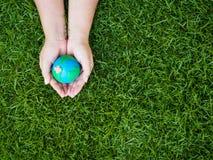 Jour de terre La terre à l'arrière-plan de mains et de champ d'herbe verte Envi Photos stock