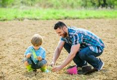 Jour de terre petit p?re d'aide d'enfant de gar?on dans l'agriculture Jour de terre heureux Arbre g?n?alogique sol naturel riche  photos libres de droits