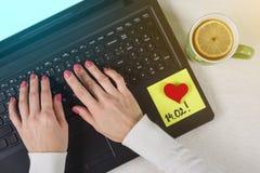 Jour de Valentine Une note du texte 14 02 écrits sur un autocollant de papier Ordinateur de fond, ordinateur portable, mains du ` Photos libres de droits