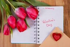 Jour de valentines écrit au carnet, aux tulipes fraîches, à la lettre d'amour et au coeur, décoration pour des valentines Photographie stock libre de droits