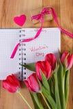 Jour de valentines écrit au carnet, aux tulipes fraîches, au cadeau enveloppé et au coeur, décoration pour des valentines Images stock