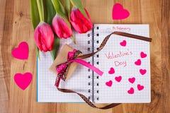 Jour de valentines écrit au carnet, aux tulipes fraîches, au cadeau enveloppé et aux coeurs, décoration pour des valentines Photographie stock