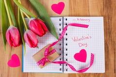 Jour de valentines écrit au carnet, aux tulipes fraîches, au cadeau enveloppé et aux coeurs, décoration pour des valentines Images libres de droits