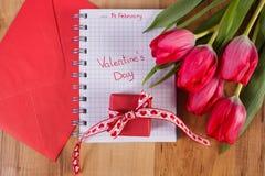 Jour de valentines écrit en carnet, tulipes fraîches, lettre d'amour et cadeau, décoration pour des valentines Photo stock