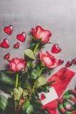 Jour de valentines, amour ou concept de datation Groupe de roses rouges avec le boîte-cadeau, la carte de voeux de papier blanc e Image libre de droits